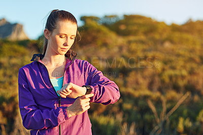 Buy stock photo Shot of a young woman checking her time while out for a trail run