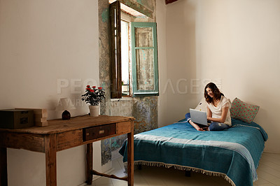 Buy stock photo Shot of a young woman sitting on her bed using a laptop