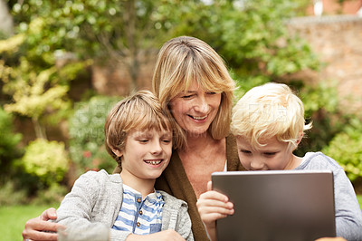 Buy stock photo Shot of a grandmother and her grandsons sitting at a table in her yard using a digital tablet