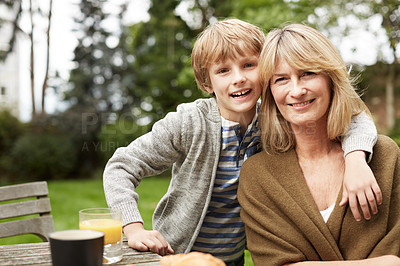Buy stock photo Portrait of a grandmother and her grandson sitting at a table in her yard
