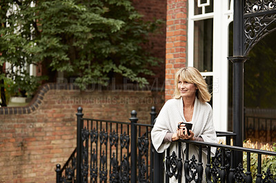 Buy stock photo Shot of a mature woman standing on her front porch drinking a cup of coffee