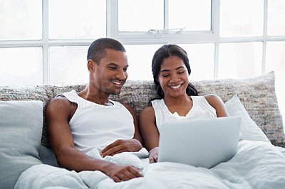 Buy stock photo Shot of a smiling young couple lying in bed using a laptop