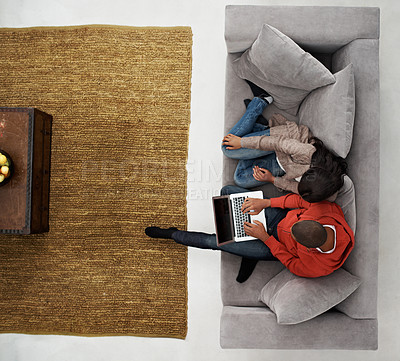 Buy stock photo High angle shot of a young couple sitting on their sofa using a laptop