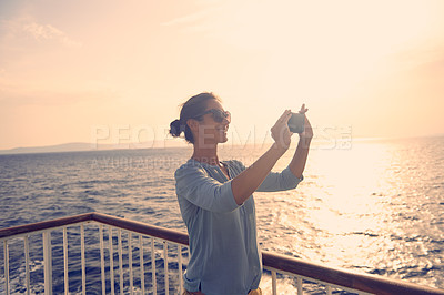 Buy stock photo Shot of a young female tourist photographing the sunset on a balcony overlooking the beach