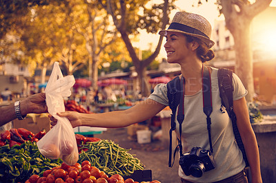 Buy stock photo Shot of a woman buying fruit and vegetables at a market in a foreign city