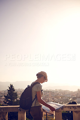 Buy stock photo Shot of a woman looking at a map while exploring a foreign city