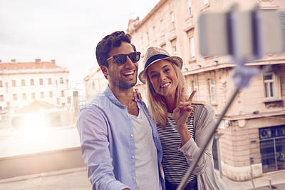 Buy stock photo Shot of a young couple taking a selfie using a selfie stick while touring a foreign city