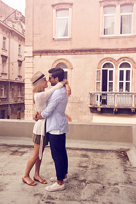 Buy stock photo Full length shot of a young couple embracing while touring a foreign city