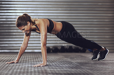 Buy stock photo Full length shot of a young woman doing push-ups at the gym
