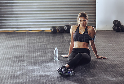 Buy stock photo Shot of a young woman sitting on the floor at the gym with her water bottle next to her