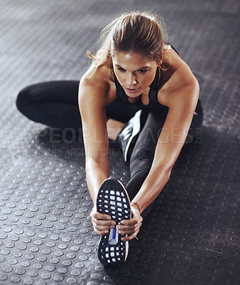 Buy stock photo Shot of a young woman stretching her legs before a gym workout