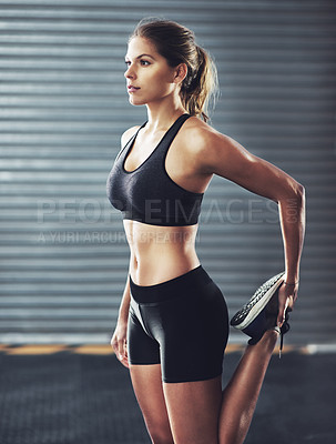 Buy stock photo Shot of a woman stretching her legs before a gym workout