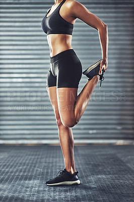 Buy stock photo Cropped shot of a woman stretching her legs before a gym workout
