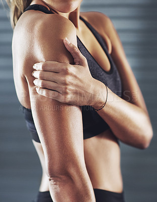 Buy stock photo Shot of a sportswoman with a shoulder injury