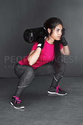 Buy stock photo Studio shot of an attractive young woman working out with dumbbells  against a gray background