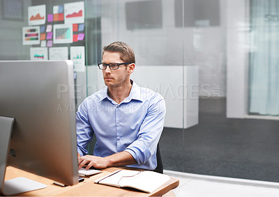 Buy stock photo Shot of a businessman working on his office computer