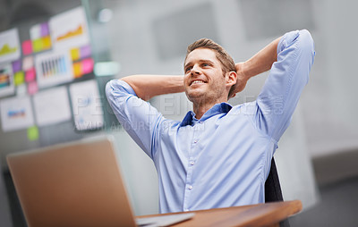 Buy stock photo Shot of a smiling businessman leaning back in his chair with his hands behind his head