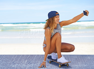 Buy stock photo Shot of a young skater taking at selfie at the beach