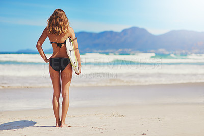 Buy stock photo Shot of a young surfer walking on the beach with her surfboard