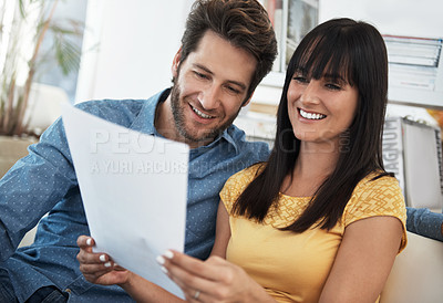Buy stock photo Cropped shot of a couple looking over some paperwork at home