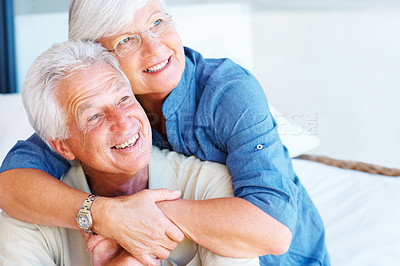 Buy stock photo Senior couple smiling and looking away with woman embracing man from behind