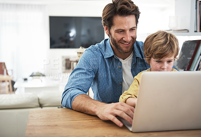 Buy stock photo Cropped shot of a young father and son using a laptop together at home