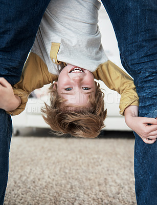 Buy stock photo Portrait of a young boy hanging upside down between his father's legs