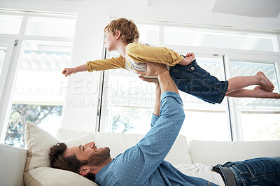 Buy stock photo Shot of a young father playing with his son on the sofa at home