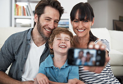 Buy stock photo Shot of a family of three taking a selfie at home