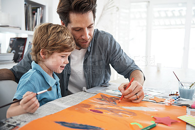 Buy stock photo Shot of a father helping his son with an art project