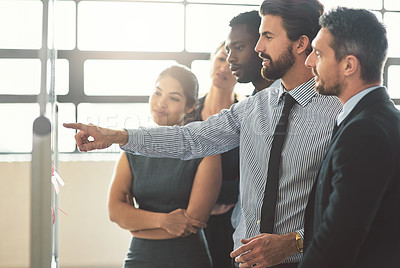 Buy stock photo Shot of a group of businesspeople looking over plans on a whiteboard