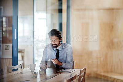 Buy stock photo Shot of a businessman using a digital tablet