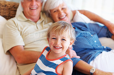 Buy stock photo Portrait of cute little kid sitting on sofa with grandparents and smiling