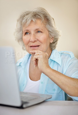 Buy stock photo A senior woman deep in thought while working on her laptop