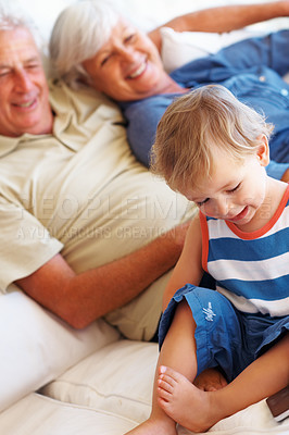 Buy stock photo Young boy sitting on sofa with grandparents and looking at the mobile phone