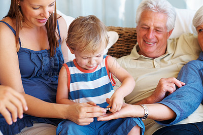 Buy stock photo Cute child sitting on a sofa with family and playing with cellphone