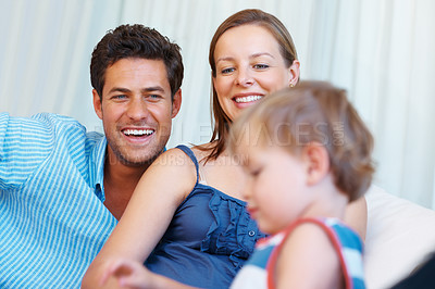Buy stock photo Happy parents smiling and looking at their little child