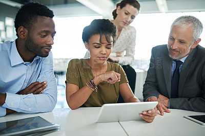 Buy stock photo Shot of a group of businesspeople talking together over a digital tablet in an office