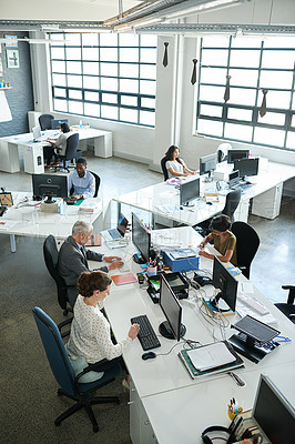 Buy stock photo Shot of a group of coworkers sitting at their workstations in an office