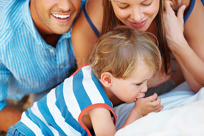 Buy stock photo Young kid lying on sofa with parents and putting thumb in mouth