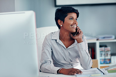 Buy stock photo Shot of a young businesswoman talking on a cellphone in her office