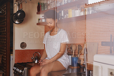 Buy stock photo Shot of a young woman using her cellphone while sitting on her kitchen counter