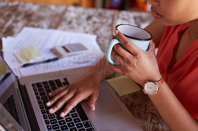 Buy stock photo Shot of a young woman drinking a coffee while working on a laptop in her kitchen
