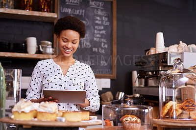 Buy stock photo Cropped shot of a young woman working in her coffee shop