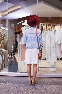 Buy stock photo Rearview shot of a young woman shopping in a clothing store