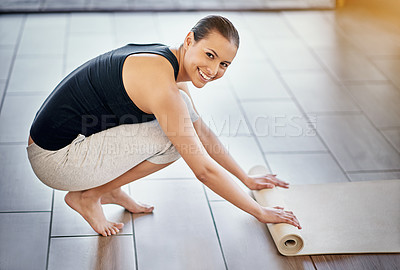 Buy stock photo Full length portrait of a of a young woman rolling out her exercise mat for yoga
