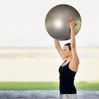 Buy stock photo Cropped shot of a young woman working out with an exercise ball