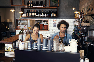 Buy stock photo Shot of two young baristas working in a coffee shop