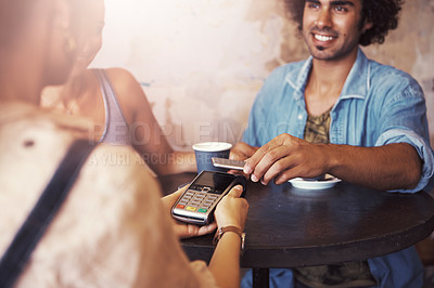 Buy stock photo Shot of a man paying for coffee with a smartphone at a cafe
