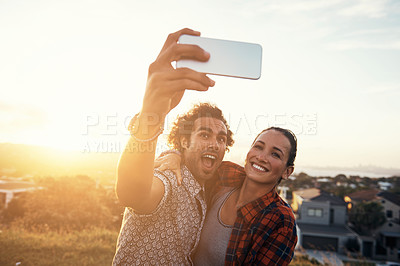 Buy stock photo Cropped shot of an affectionate young couple taking a selfie outside